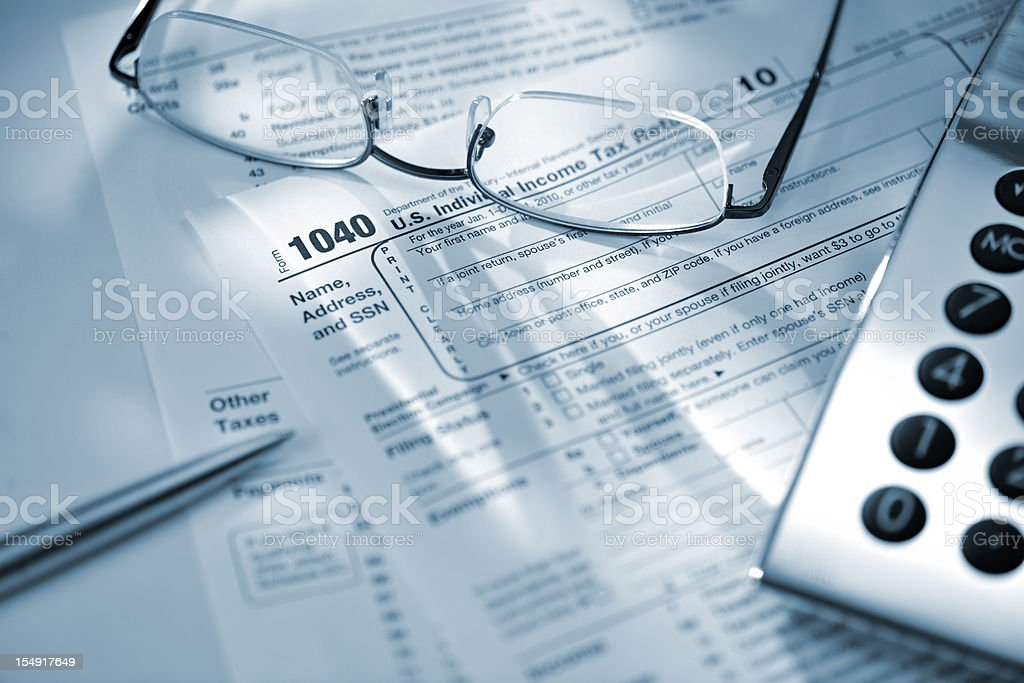 silver calculator glasses and pen on US tax return form stock photo