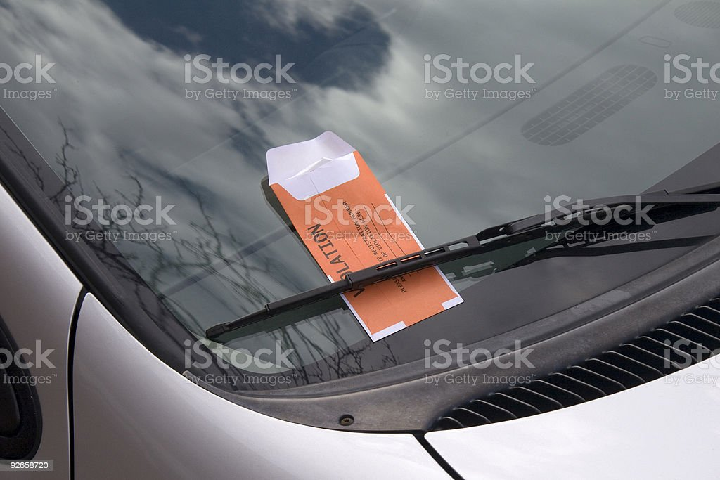 Silver car that has a parking ticket stock photo