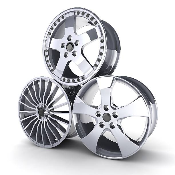 3 silver car wheels stacked against a white background stock photo