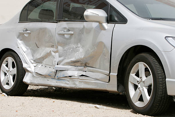 Silver car with a large dent in the side, ruining two doors stock photo