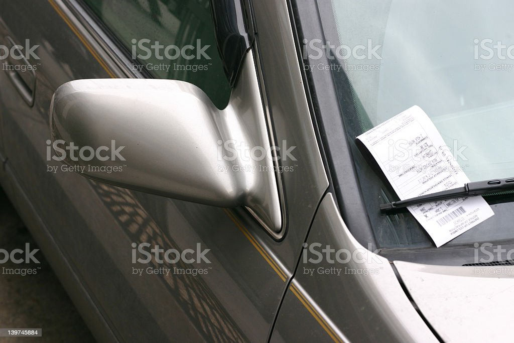 A silver car with a parking ticket on the window stock photo