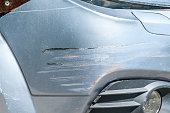 istock Silver car with scratched paint with red lines of other vehicle damaged in crash accident or parking lot, close up 958784452