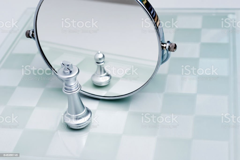 Silver chess king imagining itself as a pawn stock photo