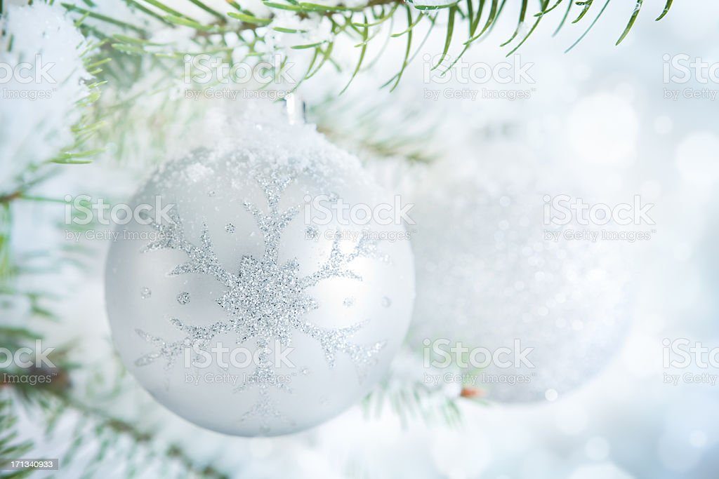 Silver Christmas baubles hanging on a Christmas tree with snow royalty-free stock photo