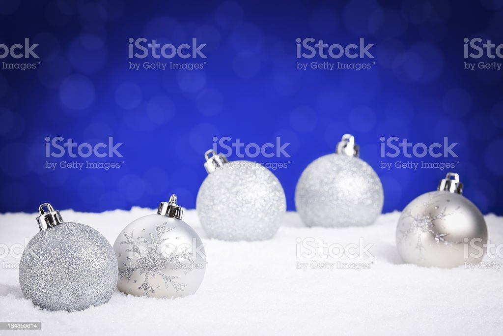 Silver Christmas baubles on snow with a blue background royalty-free stock photo