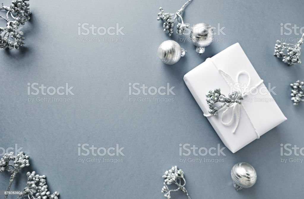 Silver christmas decorations and christmas present on gray