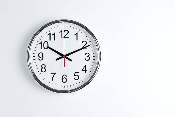 ... A silver classic wall clock on a white wall stock photo ...