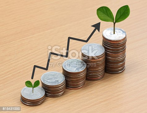 istock Silver coin stack and arrow line and have treetop in business growth concept on wood floor. 815431000