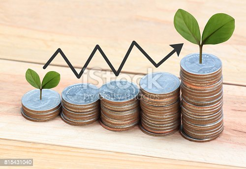 istock Silver coin stack and arrow line and have treetop in business growth concept on wood floor. 815431040