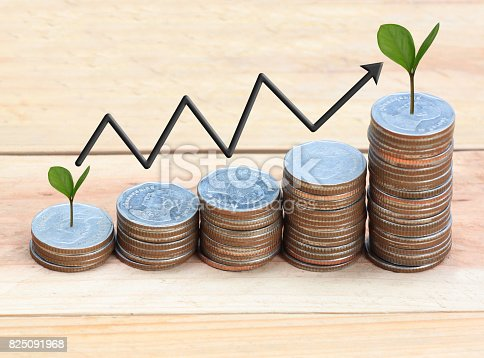 istock Silver coin stack and arrow line and have treetop in business growth concept on wood floor. 825091968
