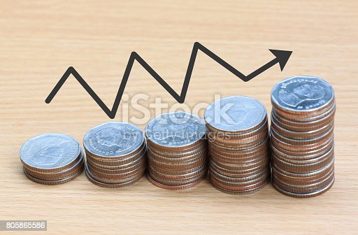 istock Silver coin stack and arrow line in business growth concept on wood floor. 805865586
