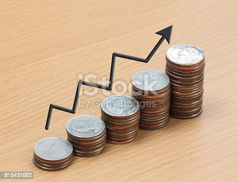 istock Silver coin stack and arrow line in business growth concept on wood floor. 815431002