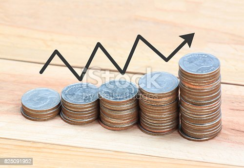 istock Silver coin stack and arrow line in business growth concept on wood floor. 825091952
