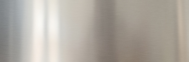 Silver colored brushed metal surface. Long metallic texture with light reflections for a technological background.