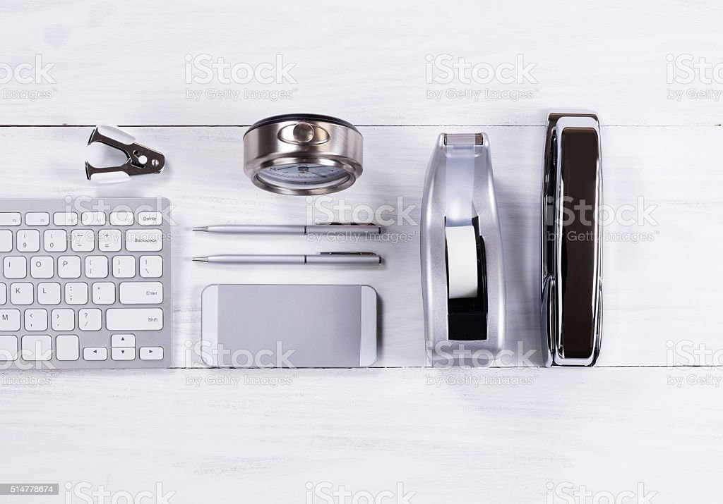Silver colored stationery objects on white wood background stock photo