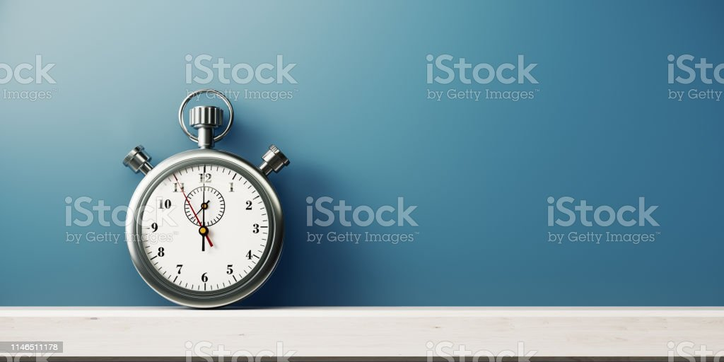 Silver Colored Stopwatch In Front of Blue Wall Silver colored stopwatch in front of blue wall. Horizontal composition with copy space. Backgrounds Stock Photo