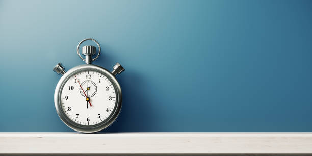 Silver Colored Stopwatch In Front of Blue Wall Silver colored stopwatch in front of blue wall. Horizontal composition with copy space. timer stock pictures, royalty-free photos & images