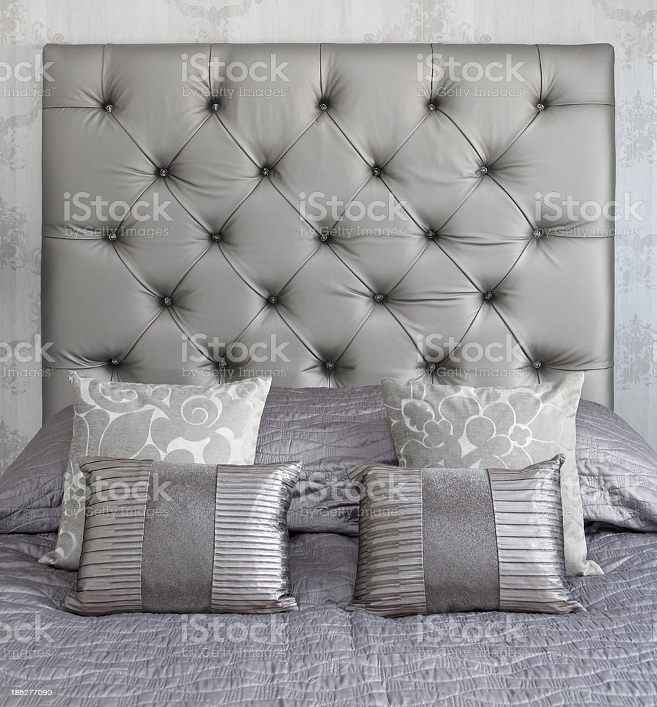 silver coloured silk cushions on a bed stock photo