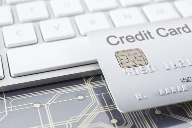 Silver credit card with digital circuits and keyboard. stock photo