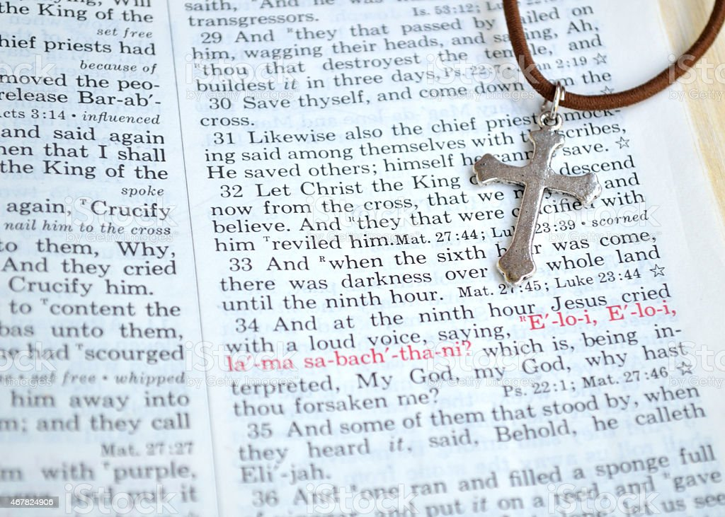 Silver cross and Good Friday Bible scripture stock photo