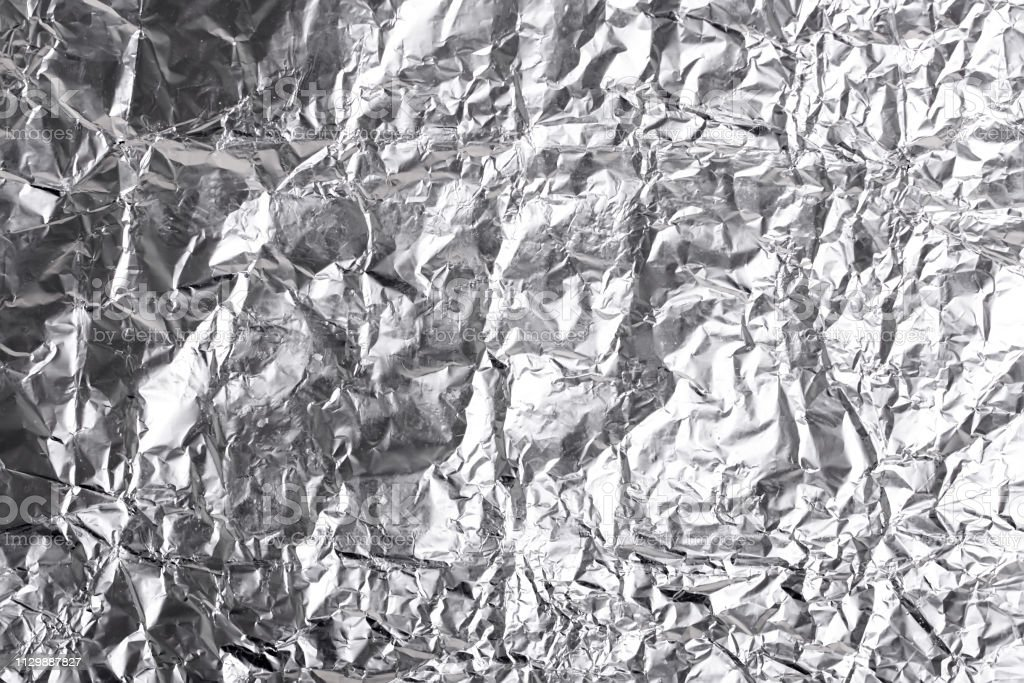 Silver crumpled foil shiny metal texture background wrapping paper...