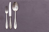 silver old cutlery on a gray plate