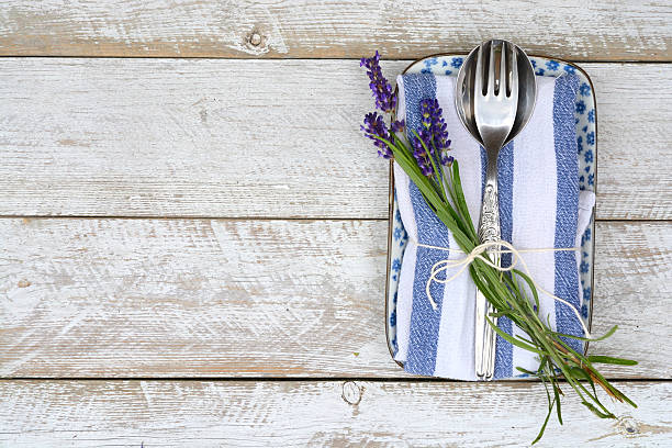 silver cutlery on blue white lavender napkin with  copy space - blue table setting stock photos and pictures