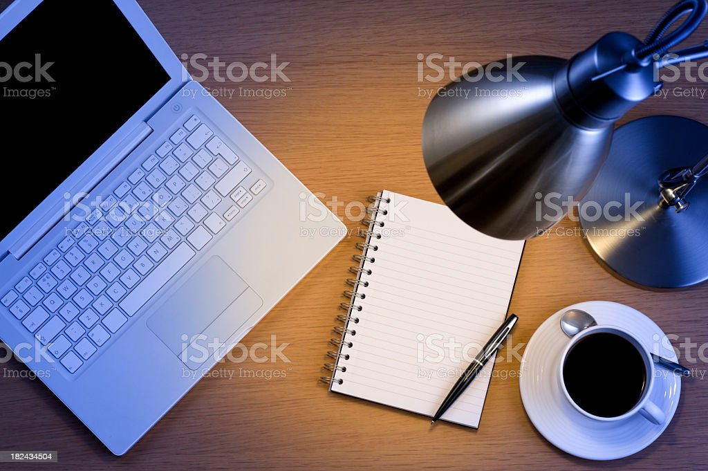 Silver desk lamp laptop pen and notepad and black coffee stock photo