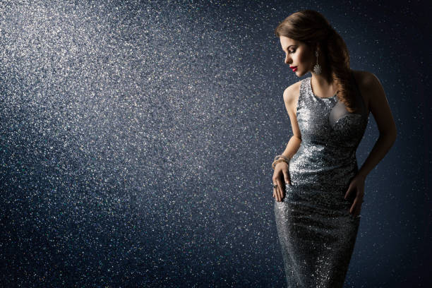 Silver Dress, Fashion Model Posing in Sparkling Sexy Gown, Woman Beauty Portrait over Lighting Sparkles Silver Dress, Fashion Model Posing in Sparkling Sexy Gown, Elegant Woman Beauty Portrait on Lighting Sparkles Background prom night stock pictures, royalty-free photos & images