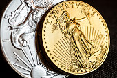 closeup of silver eagle and golden american eagle one ounce coins on black background