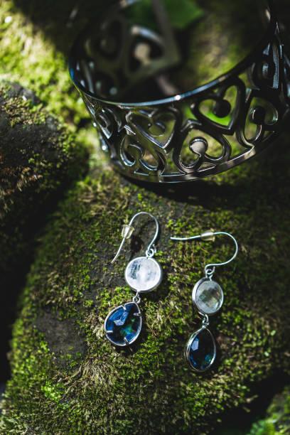 silber ohrringe mit weißen und blauen schmuckstein auf grünem hintergrund von moos closeup - ohrringe tropfen stock-fotos und bilder