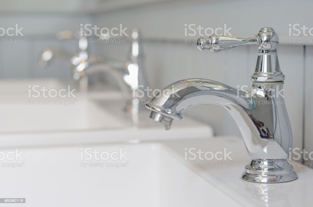 silver faucet or water tap with white washing sink in public toilet. stock photo