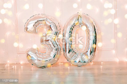 Silver foil birthday balloons number 30 with glitter lights. Birthday concept.