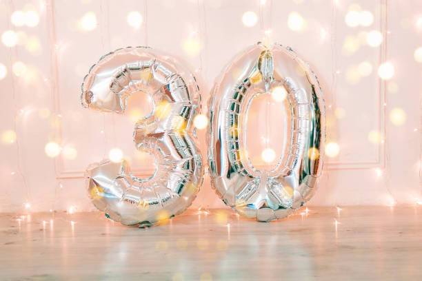 silver foil birthday balloons number 30 with glitter lights. - number 30 stock photos and pictures