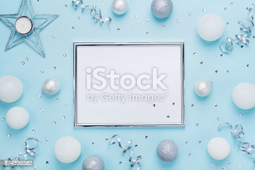 istock Silver frame and christmas decoration on stylish blue table top view. Fashion background. Flat lay. Party mockup concept. 874333382