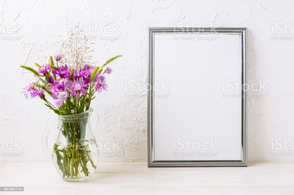 Silver frame mockup with purple burdocks in jug - foto stock