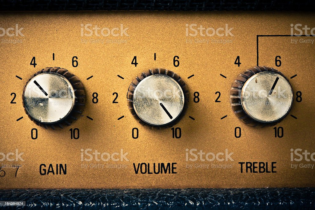 Silver gain, volume, and treble knobs on gold amplifier stock photo