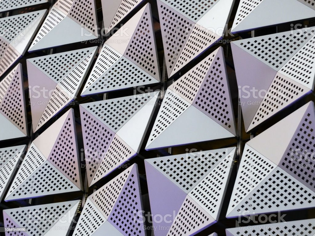 silver geometric steel cladding with angular patterns stock photo