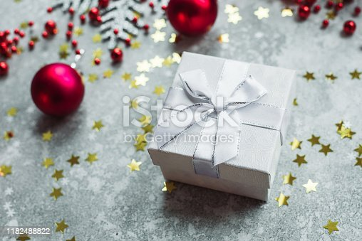 istock Silver gift with bow on grey snowy background with red Christmas balls and gold confetti stars 1182488822
