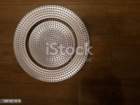 948081716 istock photo Silver glistening plate, isolated on wooden  background.Top view. 1061821816