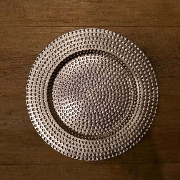 Silver glistening plate, isolated on wooden  background.Top view. stock photo