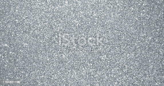 istock Silver glitter background, sparkling shimmer glow particles texture. Silver light sparks and glittering foil sequins background with shine sparks glare 1194831196