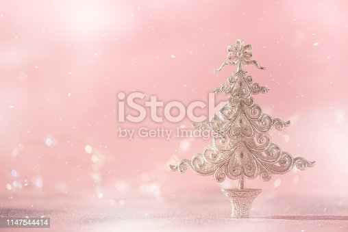 881350776 istock photo Silver glitter Christmas tree on pink background with lights bokeh, copy space. Greeting card for new year party. Festive holiday concept 1147544414