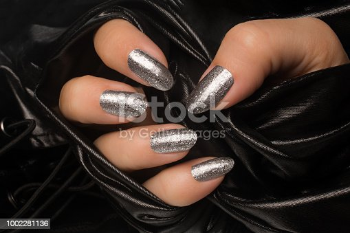 Female hand with glittered silver nails is in black textile background, manicure and nail care concept.