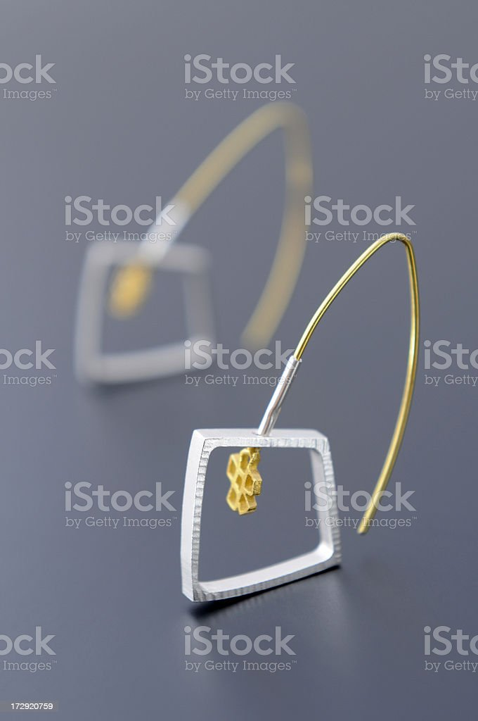 Silver - gold earring in modern design royalty-free stock photo
