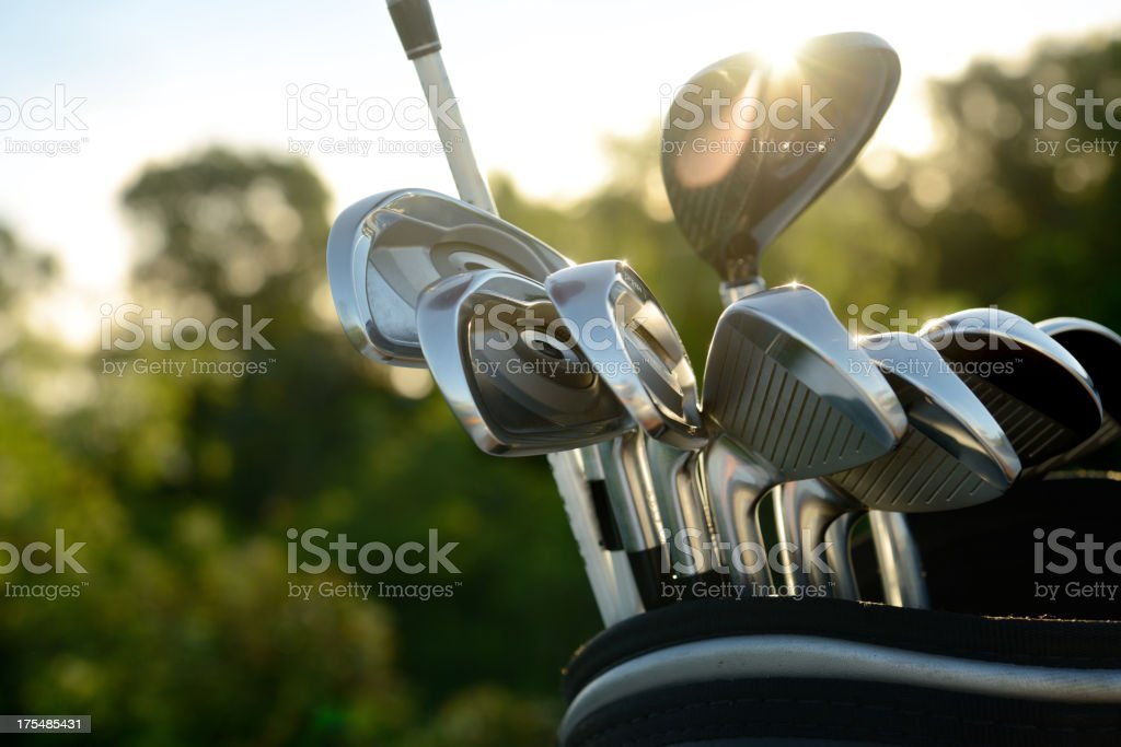 Silver golf clubs reflecting sun light stock photo