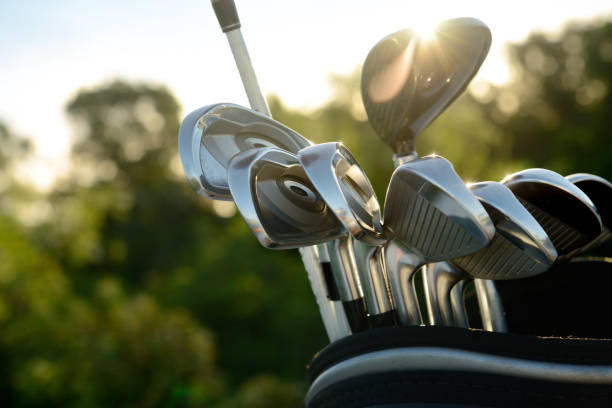 silver golf clubs reflecting sun light - golf clubs stock photos and pictures