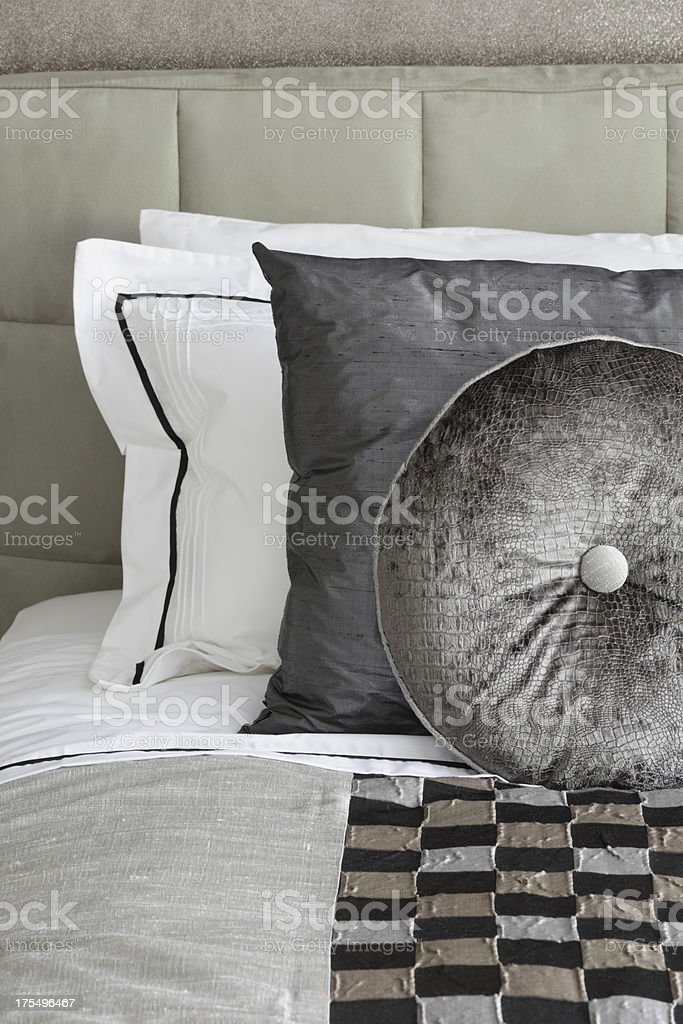 silver grey silk cushions on a bed stock photo
