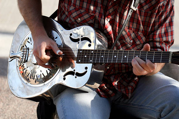 Silver Guitar A man playing a metal acoustic guitar. country and western music stock pictures, royalty-free photos & images