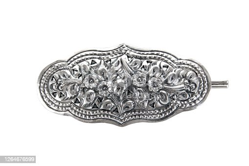 Silver hair clip isolated on white background. Silver hair clip with flowers, branches and leaves carving pattern isolated